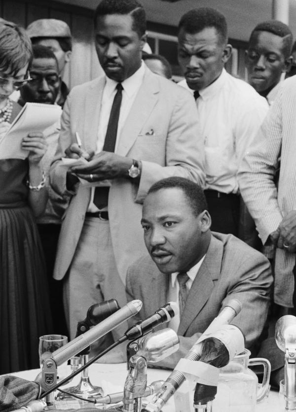 Clarence B. Jones, legal adviser to Martin Luther King Jr., takes notes behind King at a press conference regarding in Birmingham, Ala., in February 1963.