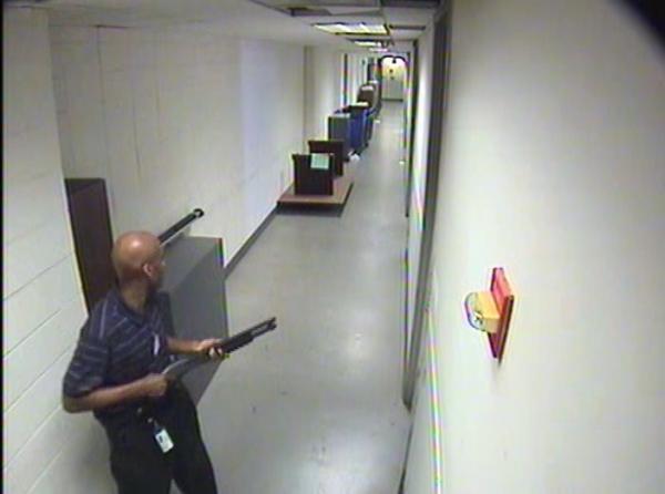 Alexis moves through the hallways of Building #197 carrying the Remington 870 shotgun.