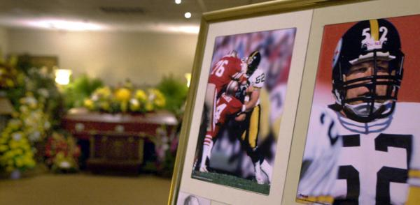 The casket bearing the body of former Pittsburgh Steelers center Mike Webster is surrounded by flowers, after funeral services in Pittsburgh in September 2002. Mark Fainaru-Wada and Steve Fainaru, authors of <em>League of Denial</em>, point to Webster's autopsy as one of the most significant moments in the history of sports.