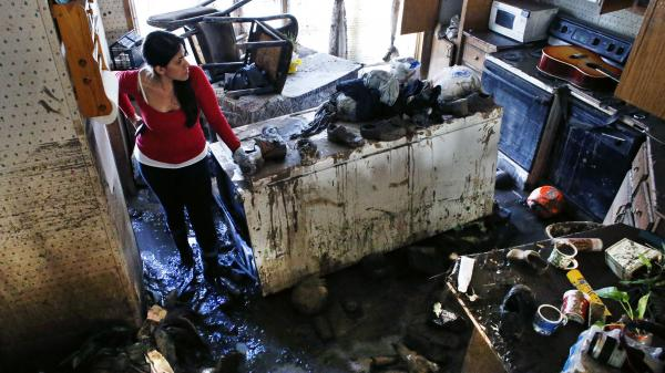 Sonia Marquez, an organizer with the Colorado Immigrant Rights Coalition, looks for keepsakes amid the muck inside one of the many flood-ravaged homes at a decimated trailer park in Evans, Colo., on Sept. 24. The majority of the residents in the trailer park are immigrants.