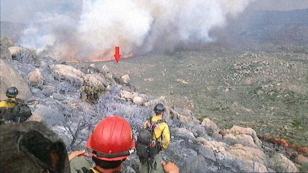 A photo taken by the Granite Mountain Hotshots on June 30 shows their position on a ridge, with a red arrow indicating the original location of their lookout. The crew's lookout was the only team member to survive the fire.