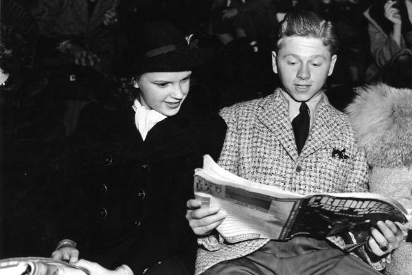Rooney and Judy Garland look over the program at the <em>Ice Follies</em>. The two starred together on screen and developed a friendship.