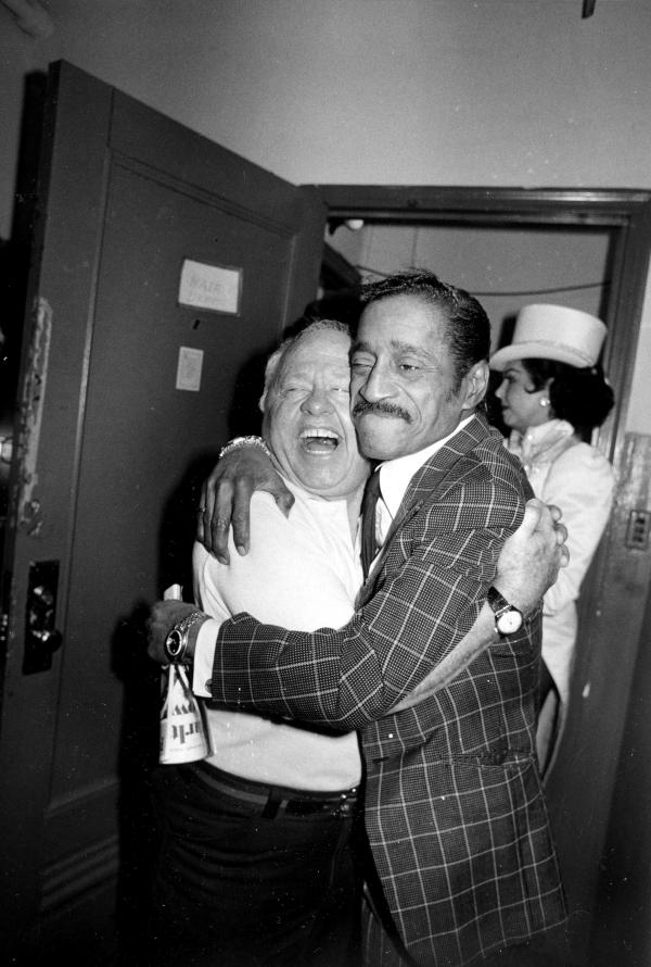Rooney gets a hug from entertainer Sammy Davis Jr. during intermission of Rooney's Broadway musical comedy revue <em>Sugar Babies</em> in 1981.