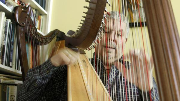 Ralph Thomas plays the harp at his house in Arlington, Vt. His reflux symptoms weren't controlled by medication, so he decided to have surgery to install a LINX device.