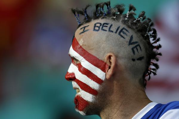 A U.S. supporter shows off his face paint before the match.