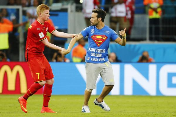 Belgium's Kevin De Bruyne restrains a pitch invader during the match.
