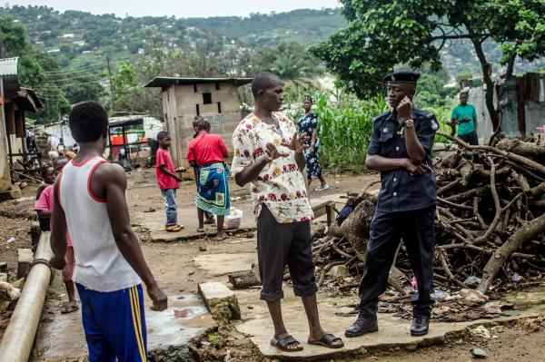 A neighbor talks to one of the two policemen assigned to enforce the quarantine of Sule Koroma's house in Freetown, Sierra Leone.