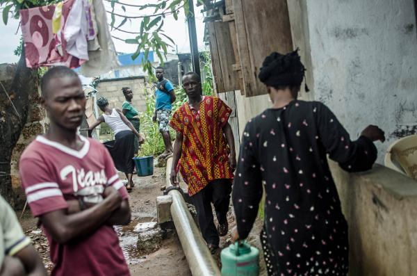Saudatu Koroma's mother, Hana Conteh (right), leaves the quarantined house to collect water, while her father, Mohamed Koroma (center), returns.