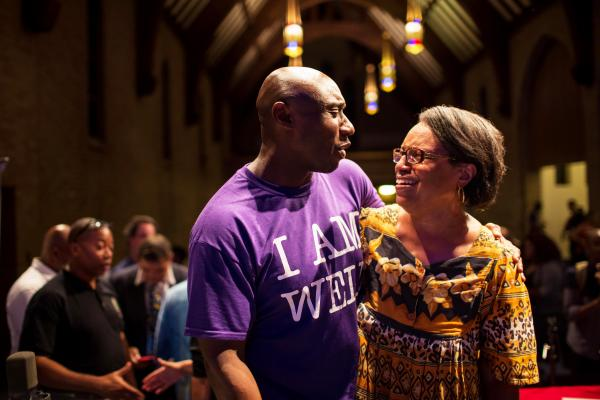 "The Rev. Willis Johnson (left), pastor of Wellspring Church in Ferguson, speaks to the Rev. Michele Shumake-Keller after the panel discussion in Ferguson, Mo., on Thursday. Johnson said he hoped the event would be a step to healing a ""community in trauma."""
