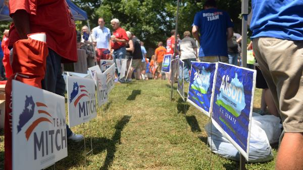 Political signs separate Sen. Mitch McConnell's and Alison Lundergan Grimes' camps at the annual Fancy Farm picnic in Kentucky in August.