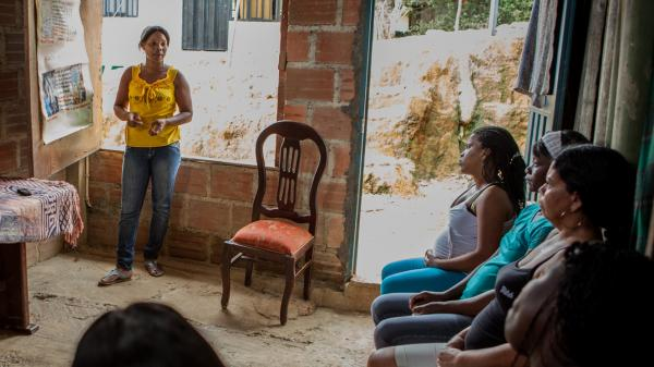 Neighbors come and listen as Maritza Yaneth Asprilla gives a workshop on women's health at her home in Buenaventura, Colombia.