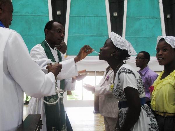 Priests use tweezers to deliver the Holy Communion wafer at Trinity Cathedral in Monrovia to prevent the spread of Ebola.