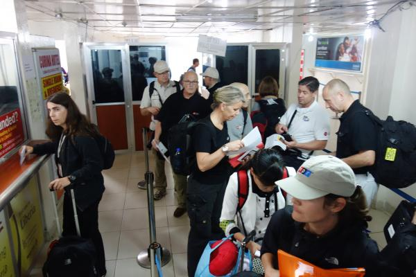 Our blogger Michaeleen Doucleff (in NPR cap) waits in line at Liberia's Roberts International Airport.