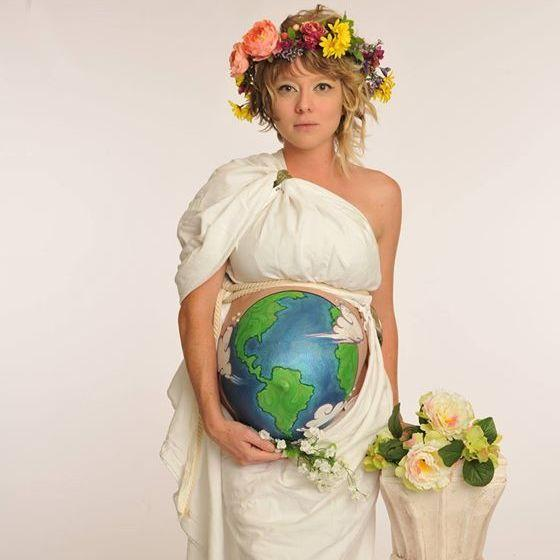 "Heather Nicole Artrip — who lives in Stuart, Fla., and listens to NPR member station WQCS — dresses as Mother Earth for Halloween. ""I made the head piece and toga from thrift store finds,"" Heather says. ""It took me awhile to figure out a good way to wear the sheet and have it and expose my midsection. Then my friend painted the Earth on my big pregnant belly."