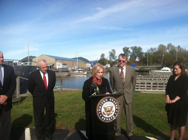 Sen. Kirsten Gillibrand (D-NY) discusses the impact of microbeads on the environment. Oswego Mayor Tom Gillen (left) and Port of Oswego Board Chairman Terry Hammill (right) attended.