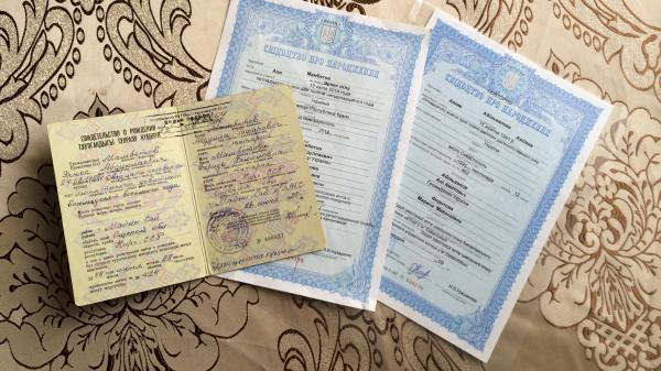 The top document is Ernes Ayserezli's Soviet birth certificate. His wife, born after the Soviet Union collapsed, has a Ukrainian one – the very same Ukrainian document that the couple wanted so badly for their infant son, Ali. They made it just in time, before the hospital began printing Russian ones.
