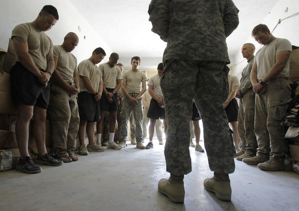 Soldiers pray with a chaplain in Afghanistan. Jason Torpy says military chaplains are assigned many secular advising duties that atheist service members need, too.