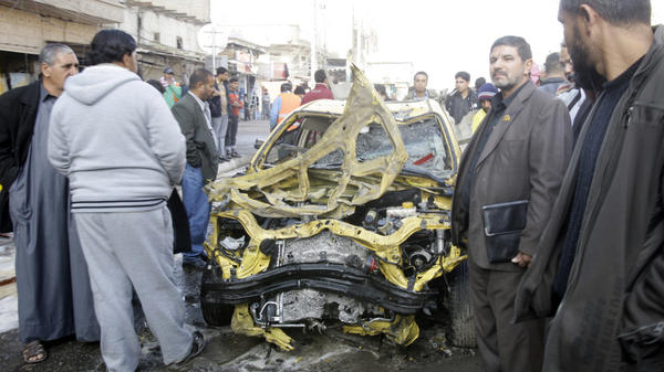 Iraqi men examine some of the wreckage left behind after one of today's explosions in Baghdad.