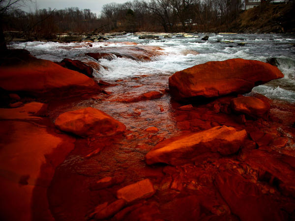 Rocks on the shore of the Lackawanna River in Duryea, Pa., are discolored by iron oxide and sulfur compounds — pollutants left behind by past coal mining in the state.