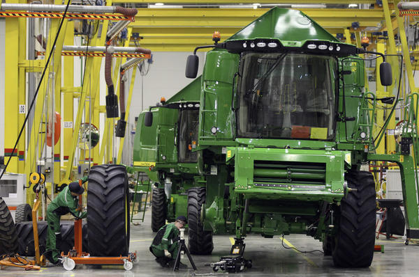 Employees fit a tire to a John Deere W540 combine inside the company's Domodedovo manufacturing center near Moscow, Russia. The tractors are built in Waterloo, Iowa, and then taken apart and shipped to the Russian plant for reassembly.