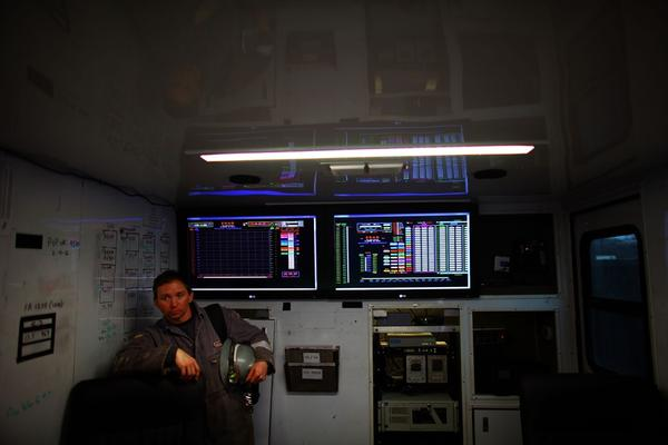 A Chesapeake Energy worker stands next to the control panel that monitors the fracking process.