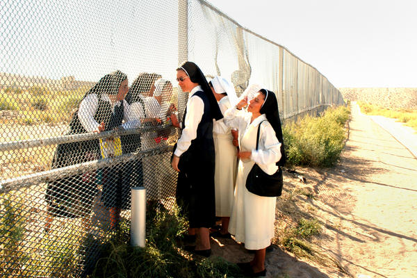 <em>Sisters at the Border, </em>2007. Nuns meet at the border of Anapra, N.M. (left), and Barrio Anapra, Juarez. The nuns in Mexico cannot cross for various reasons — except on the day of a Mass for immigrants, held every November in the U.S.