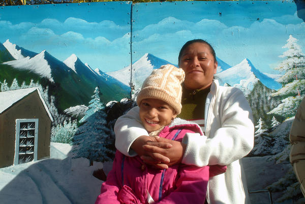 <em>Las Sierras de Juarez,</em> 2006. A mother and daughter in the Plaza de Juarez in front of a photographer's backdrop.