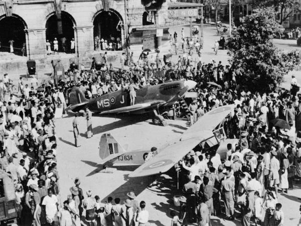 A crowd surrounds a British Spitfire and an Auster in the courtyard of the Civic Hall in Rangoon, Burma, on April 3, 1946.