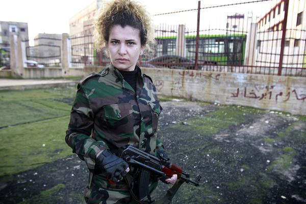 A Syrian National Defense force woman who just finished training, holds a rifle at the training center in Wadi al-Dahab in the Syrian city of Homs, on Jan. 21.