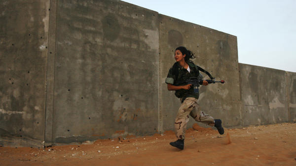 A female Israeli soldier runs during an urban warfare exercise at an army training facility near Zeelim, Israel, on June 19, 2008.