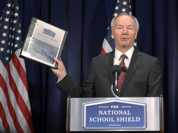 Former Republican Congressman Asa Hutchinson holds up his task force's report during a news  conference Tuesday in Washington, D.C.