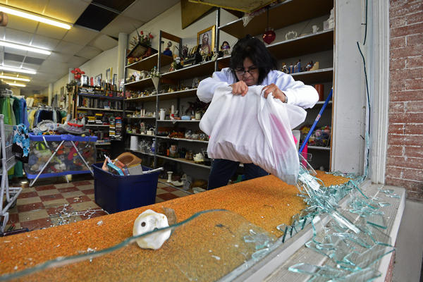 Maria Galvin cleans up broken glass in the front of her business, after the windows was blown out by the explosion.