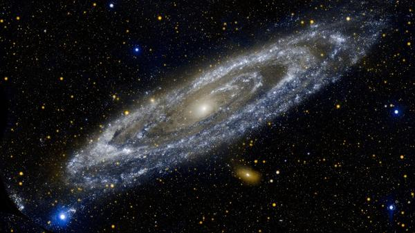 """The Galaxy Next Door"" — This composite image of the Andromeda galaxy was produced by NASA's Galaxy Evolution Explorer, showing Andromeda's ultraviolet side. NASA sent a decommission command to the space telescope Friday."
