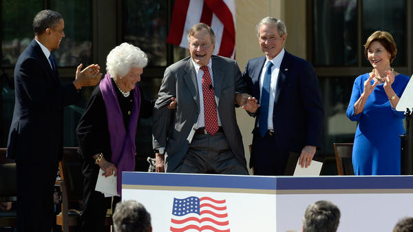 President Obama applauds as former first lady Barbara Bush and former President George W. Bush help President George H.W. Bush stand at the opening ceremony of the George W. Bush Presidential Library on April 25 in Dallas. Former first lady Laura Bush looks on.