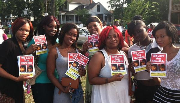 East Cleveland residents hold up flyers of Shirellda Terry at a Friday vigil at 146th & St. Clair (Brian Bull/WCPN)