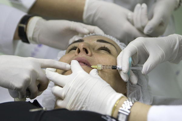 """Today society accepts the idea of improving one's image,"" says Dr. Ivo Pitanguy, Brazil's most famous plastic surgeon. Here a patient receives an injection of hyaluronic acid to plump up her lips at the Brazilian Society for Aesthetic Medicine in Rio de Janeiro in 2008."