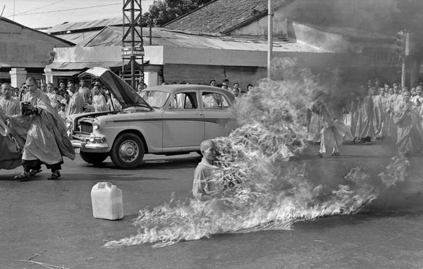 "In the first of a series of fiery suicides by Buddhist monks, Thich Quang Duc burns himself to death on a Saigon street to protest persecution of Buddhists by the South Vietnamese government, June 11, 1963. The photograph aroused worldwide outrage and hastened the end of the Diem government. With the photo on his Oval Office desk, President Kennedy reportedly remarked to his ambassador, ""We're going to have to do something about that regime."" (Malcolm Browne/AP)"