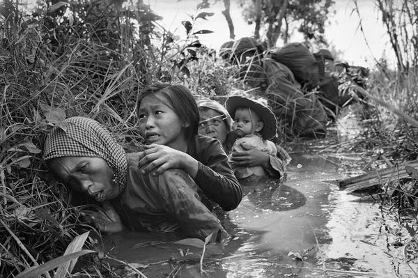 Women and children crouch in a muddy canal as they take cover from intense Viet Cong fire, January 1, 1966. Paratroopers of the 173rd Airborne Brigade (background) escorted the civilians through a series of firefights during the U.S. assault on a Viet Cong stronghold at Bao Trai, about twenty miles west of Saigon. (Horst Faas/AP)