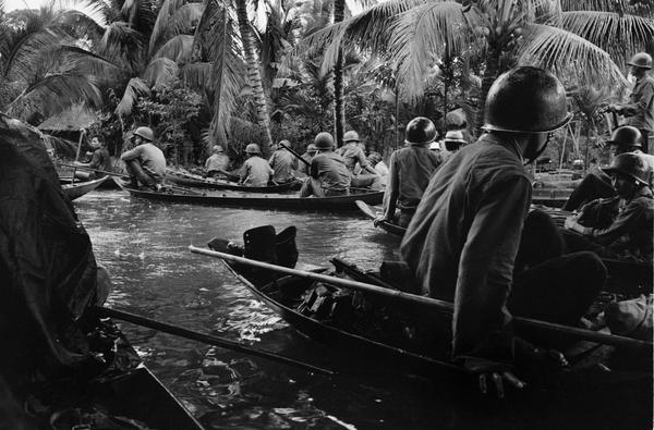 Caught in a sudden monsoon rain, part of a company of about 130 South Vietnamese soldiers moves downriver in sampans during a dawn attack on a Viet Cong camp, January 10, 1966. Several guerrillas were reported killed or wounded in the action thirteen miles northeast of Can Tho, in the flooded Mekong Delta. (Horst Faas/AP)