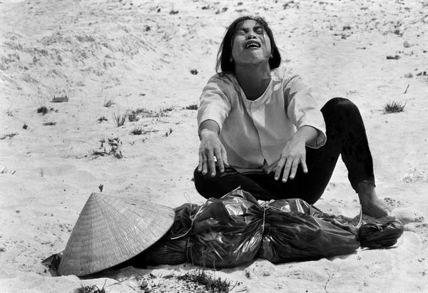A woman mourns over the body of her husband after identifying him by his teeth, and covering his head with her conical hat. The man's body was found with forty-seven others in a mass grave near Hue, April 11, 1969. The victims were believed killed during the insurgent occupation of Hue as part of the Tet Offensive. (Horst Faas/AP)