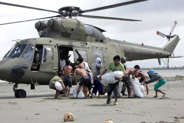 Typhoon survivors in the coastal village of Capiz, in the Philippines, carry sacks containing relief goods delivered by the Armed Forces of the Philippines.
