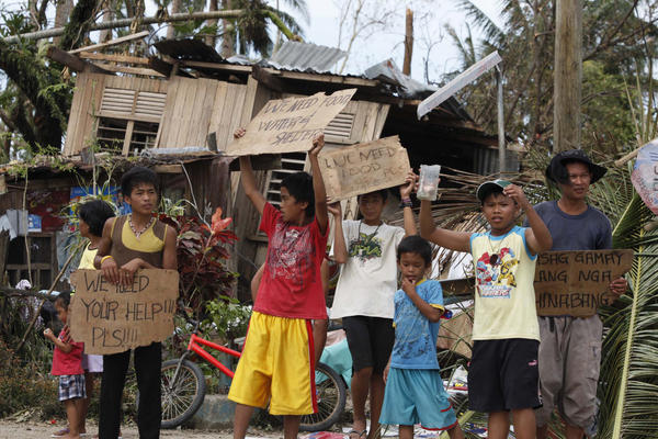 "Children ask for help and food along the highway in Cebu Province, Philippines. ""It's absolute bedlam right now,"" Richard Gordon, head of the Philippine Red Cross, told the BBC."