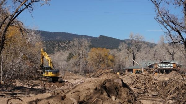 Excavators work to restore the original channel of Left Hand Creek. The creek's diversion structures sit clogged with mud, debris and stagnant water.