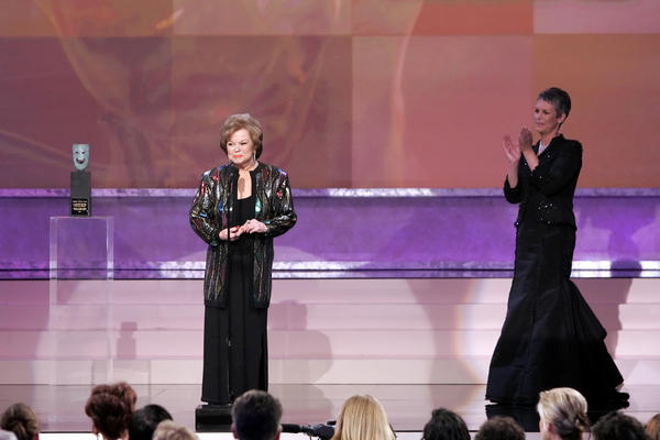 Temple accepts the Screen Actors Guild annual life achievement award in 2006 as presenter Jamie Lee Curtis applauds.