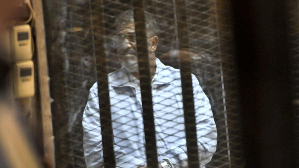 Egypt's ousted President Mohammed Morsi stands inside a glassed-in defendant's cage on Jan. 28 during his trial on charges related to the prison breaks at the height of the 18-day 2011 uprising against his predecessor Hosni Mubarak.
