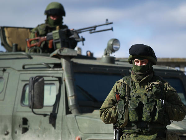 Armed men, believed to be Russians, stand guard near the Ukrainian military base in Perevalnoye outside Simferopol, on Monday.