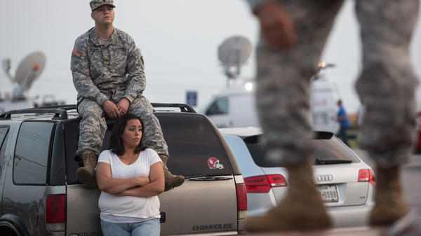 Lucy Hamlin and her husband, Spc. Timothy Hamlin, wait for permission to re-enter the Fort Hood military post, following a shooting there Wednesday.