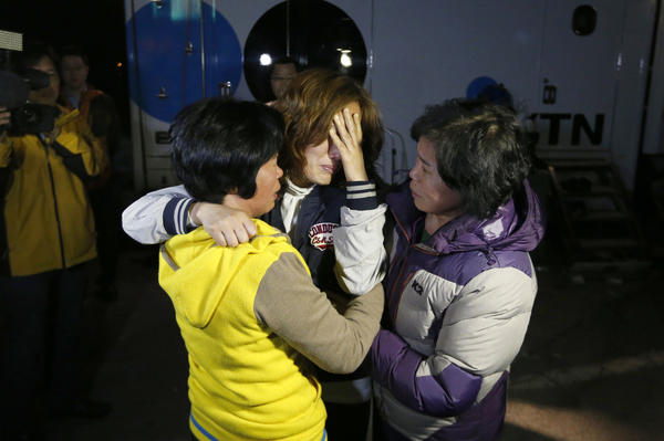 Family members of missing passengers wait for a rescue team in Jindo, South Korea, after a ferry capsized Wednesday. The Sewol was believed to have been carrying more than 450 passengers, mostly high school students and teachers, when it sank en route to the resort island of Jeju.