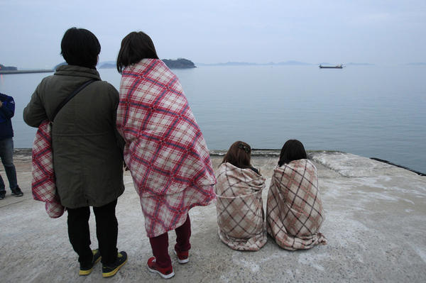 Relatives look toward the sea at Jindo. By the time rescuers arrived on the scene, the ferry was on its side.