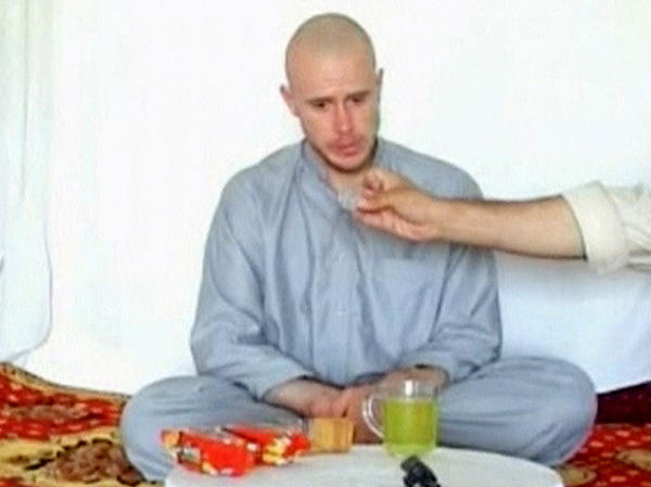 U.S. Army Sgt. Bowe Bergdahl watches in July 2009 as one of his captors displays Bergdahl's identity tag during the first of several videos the Taliban released of the soldier.